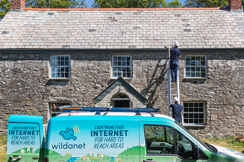 wildanet van pictured with workmen fitting broadband to cottage